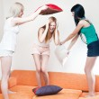 Young women fighting on pillows — Stock Photo