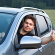 Young man looking out of car — Stock Photo