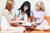 Three young women reading book — Stock Photo