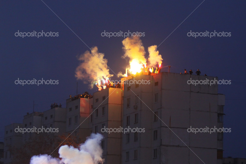 FC Dynamo Kyiv ultras burn flares on the housetop near the stadium during Ukraine Championship game against FC Obolon on APRIL 14, 2010 in Kyiv, Ukraine  Stock Photo #2921180