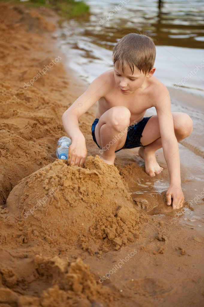 The boy builds on sand — Stock Photo #3379750