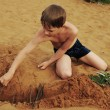 The boy builds on sand — Stock Photo #3388521