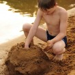 Stock Photo: The boy builds on sand