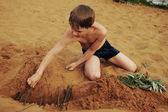The boy builds on sand — Stock Photo