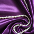 Stock Photo: White pearls on lilac silk background
