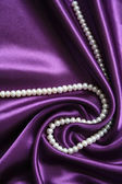 White pearls on a lilac silk background — Stock Photo