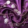Stock Photo: Lilac pearls on lilac silk