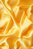 Smooth elegant golden silk — Stock Photo