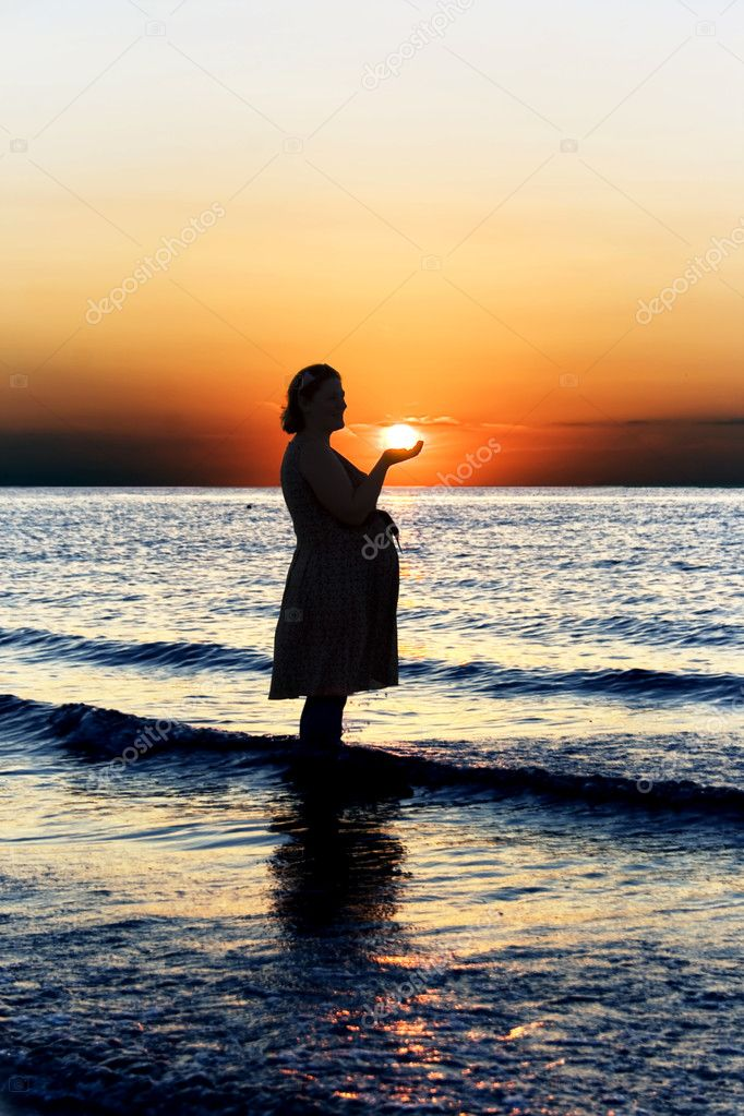 Pregnant woman on sunset background in Baltic sea — Stock Photo #3544017