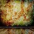 A rusty metal wall in the old room with wooden floor - Stockfoto