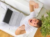 Widok z góry szczęśliwy młody człowiek siedzi na kanapie i korzysta z laptopa — Zdjęcie stockowe