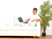 Smiling young man working on laptop computer at home — Stock Photo