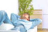 Relajarse en el sofá en casa joven — Foto de Stock