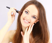 Attractive young woman applying blusher — Stok fotoğraf