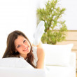 Smiling girl lying down on divan and thinking — Stock Photo #3070152