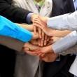 Group of business making a pile of hands in a light and modern offic - Stock Photo