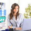 Portrait of a beautiful business woman working at her desk with a headset a — 图库照片