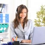 Portrait d'une femme d'affaires belle travaillant à son bureau avec un casque un — Photo