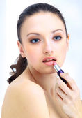 Portrait of beautiful woman applying lipstick using lip concealer brush — Stock Photo