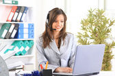 Portrait of a beautiful business woman working at her desk with a headset a — Stock Photo