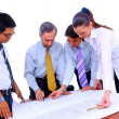 Business men and women working on blue prints — Stock Photo