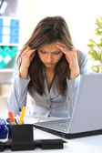 Yuong woman holding head in pain in office — Stock Photo