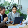 Team of multi ethnic business discussing work - Stock Photo