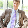 Happy businessman standing with hands in pocket — Stock Photo #3232004