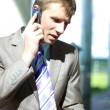 Happy young business man talking on a mobile phone — Stock Photo #3232029