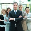 Foto Stock: Confident mature business man with colleagues at the background