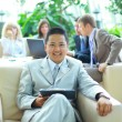 Royalty-Free Stock Photo: Asian business man with colleagues at a conference in the background