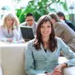Business woman sitting in office with coworkers working in the background - Stok fotoğraf