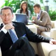 Senior business relaxed on a chair with his colleagues — Stock Photo