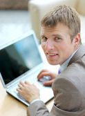 бизнесмен сидел на столе в офисе, работа с портативного компьютера, смотрю — Стоковое фото
