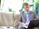 Casual looking businessman working on laptop — Stok fotoğraf