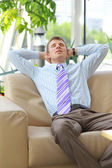 молодые расслабленной деловой человек с руками за голову на работе — Стоковое фото