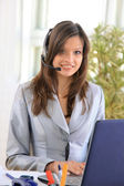 Beautiful business woman working at her desk with a headset and laptop — Stok fotoğraf