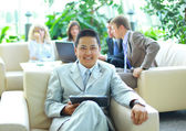 Asian business man with colleagues at a conference in the background — Stock Photo
