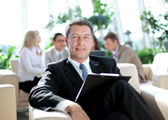 Happy business man with colleagues at a conference in the background — Stock Photo