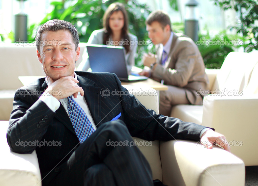 Senior business relaxed on a chair with his colleagues  — Stock Photo #3233574