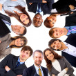 Group of business standing in huddle, smiling, low angle view — Stock Photo #4179546