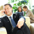Concentrating businessman on call, coworkers talkling in background — Stock Photo #4222020