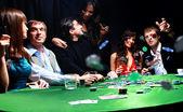Jovem fichas jogando na mesa enquanto jogando cartas — Foto Stock