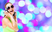 Woman in green shirt and sunglasses listening for the music using headphon — Stock Photo
