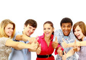 Happy guys and girls expressing happiness by showing thumbs while smiling — Stock Photo