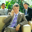 Business man speaking on the cell phone while in a meeting — Stock Photo