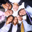Group of business standing in huddle, smiling, low angle view — Stock Photo