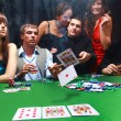 Stock Photo: Stylish man in black suit folds two cards in casino poker at Las Vegas over