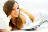 Full length of a young lady lying on sofa reading book — Stock Photo