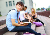 Closeup of happy young boy sitting with friends — Stock Photo
